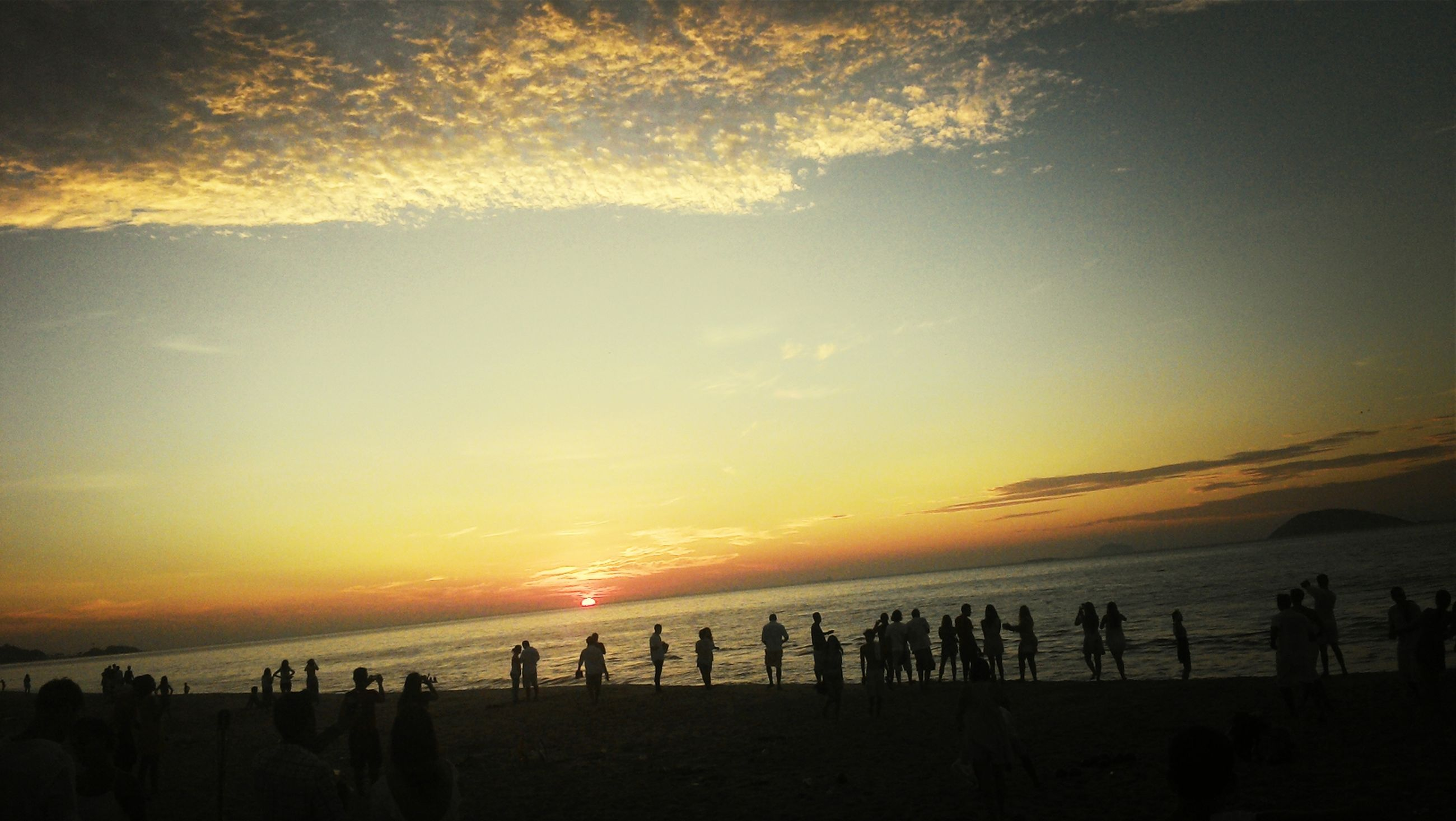 sea, sunset, beach, large group of people, horizon over water, scenics, water, sky, beauty in nature, tranquil scene, silhouette, tranquility, vacations, shore, orange color, nature, idyllic, tourist, tourism