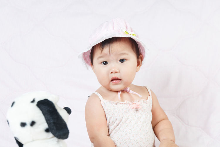 Cute baby girl sitting on bed at home