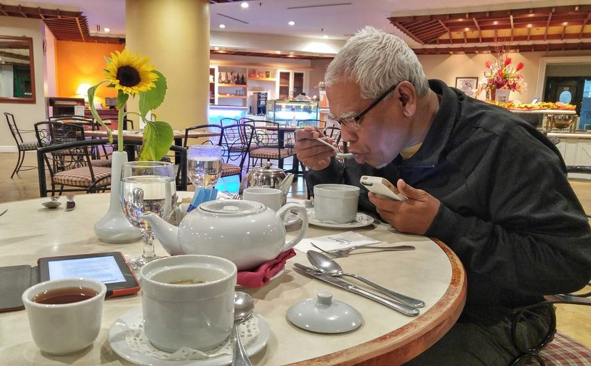 Old man drinking a soup while browsing a phone Cameron  Malaysia Old Man Drinking Soup Holding Browsing Phone Technology Tea Eyeglasses  Gray Hair Working Men Senior Adult Working Seniors Concentration Motion Looking Down Activity Tea Saucer Latte Tea Cup Coffee Herbal Tea