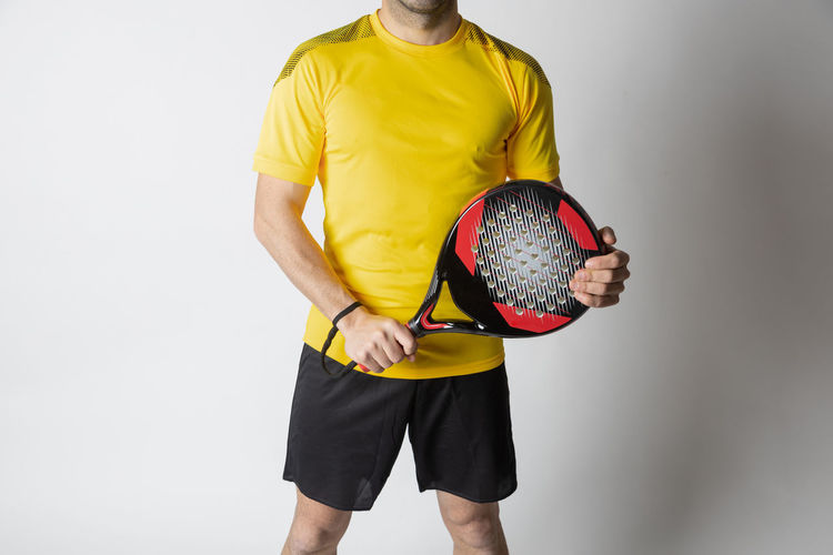Midsection of man holding ball while standing against white background