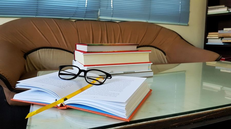 Close-up of eyeglasses and stacked books on table