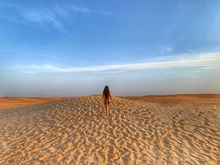 Rear view of seductive woman walking on sand in desert against sky