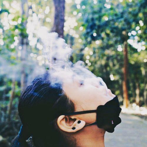 Close-up young woman smoking outdoors