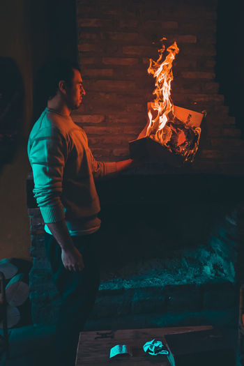 Midsection of man with fire burning at night