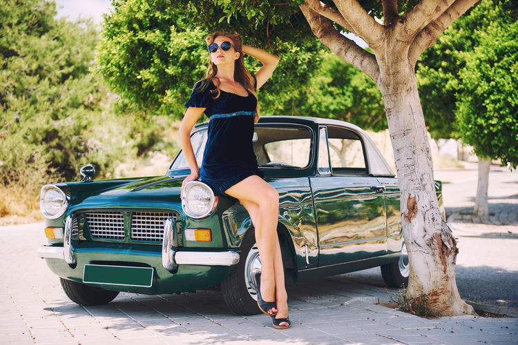 Beautiful happy woman pose near vintage car. Automobile Blonde Driver Slim Summertime Transportation Tree Woman Attractive Auto Beautiful Woman Caucasian Eyeglasses  Eyewear One Person Outdoors Pose Retro Car Retro Styled Sexygirl Short Dress Summer Vintage Cars Young Adult Young Women
