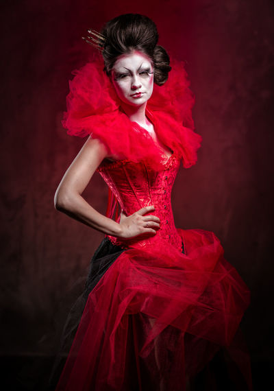 Red Queen. Woman with creative make-up in fluffy red dress posing indoors Alice In Wonderland Corset Crown Dress Elégance Face Art Fairy Tale Female Hairstyle Indoors  One Person Pose Posing Posing For The Camera Queen Of Hearts Red Red Background Red Dress Red Queen Stage Costume Studio Shot Woman Wonderland