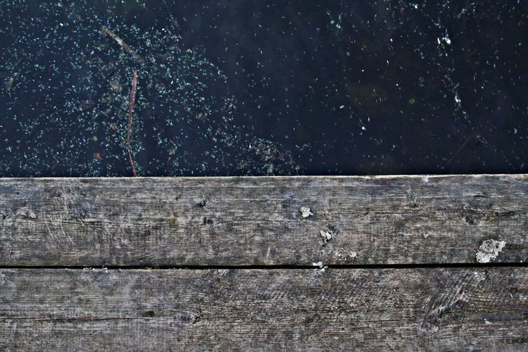 Directly above shot of lake and wooden plank
