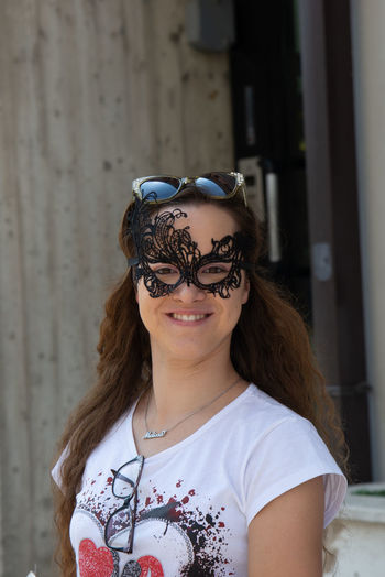 Portrait of smiling woman wearing masquerade mask standing against built structure