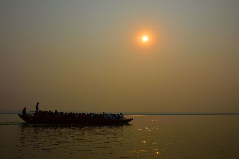 People in boat sailing on river against clear sky during sunset