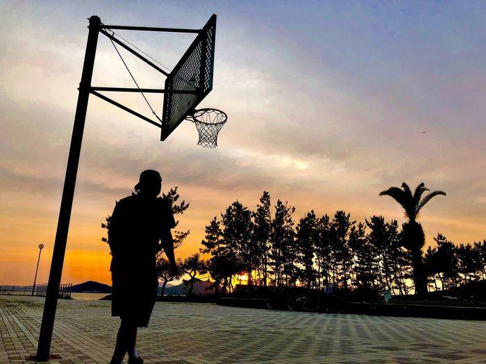 このリングの元、いろいろなドラマがあったろう。彼は少年達を見守り、その少年達も大人になった Silhouette Sky Sunset Real People Leisure Activity Lifestyles EyeEmNewHere Orange Color Men Beach Outdoors Basketball - Sport First Eyeem Photo