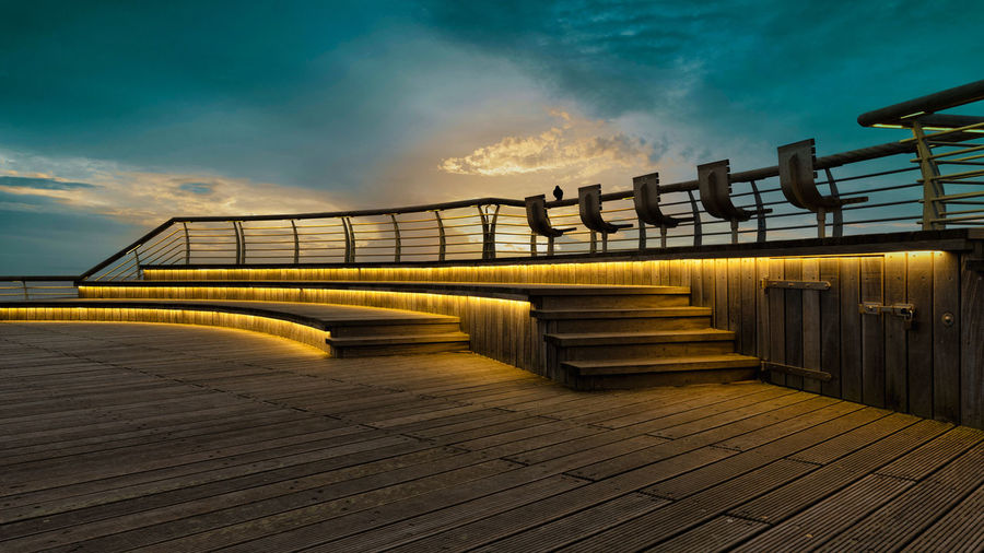 View of bridge on boardwalk against sky during sunset