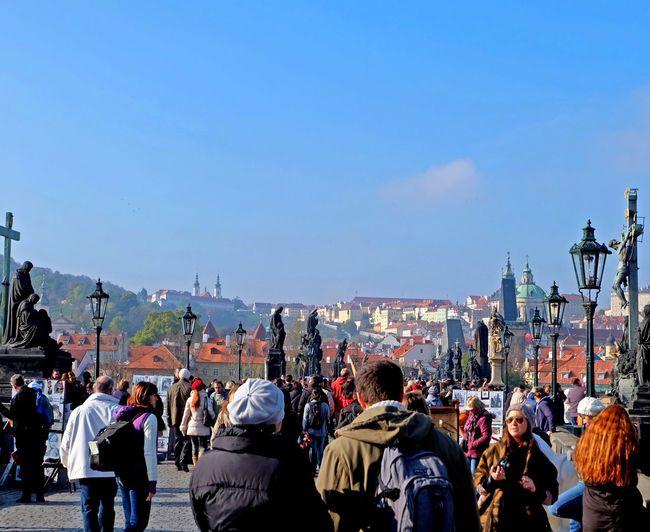 Crowd walking on charles bridge against sky