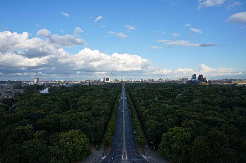 Road Amidst Tiergarten Leading Towards City Against Sky