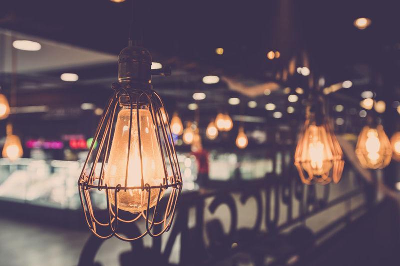 Close-up of illuminated light bulb hanging on ceiling