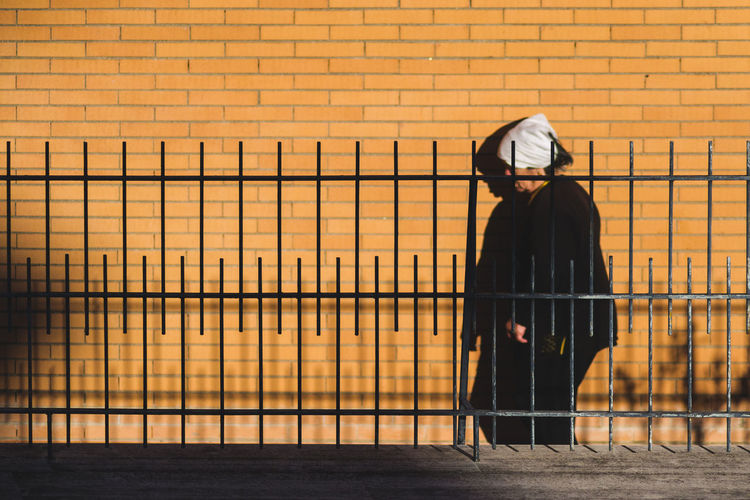 Man standing by railing against orange wall