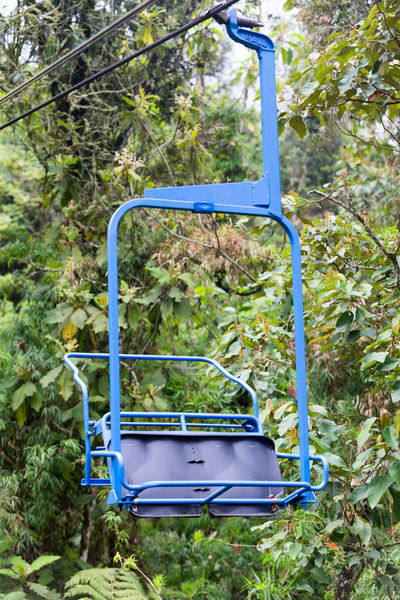 A closeup of a blue chair on the ski lift at the Recinto del Pensamiento nature reserve near Manizales, Colombia. Chair Cloud Colombia Electric Green Latin Manizales Recinto Ski Lift South America Andean Cloud Forest Coffee Triangle Colombian  Colorful Day Fog Forest Lift Mist Nature Outdoors Park Pensamiento