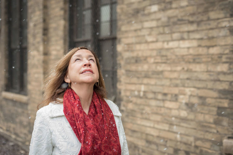 Woman standing by brick wall during snowfall