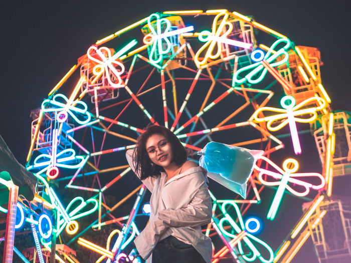 Portrait of woman with illuminated ferris wheel in amusement park