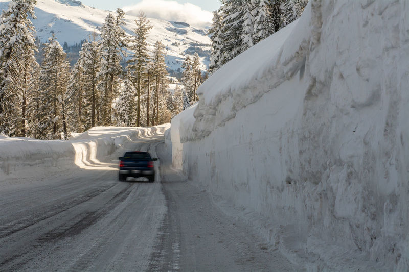Cars on road by snowcapped mountains during winter