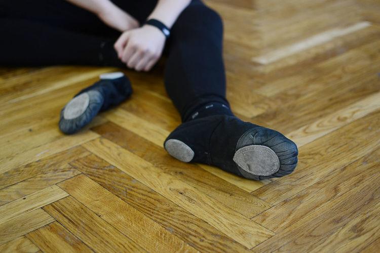 Low Section Of Dancer Sitting On Hardwood Floor