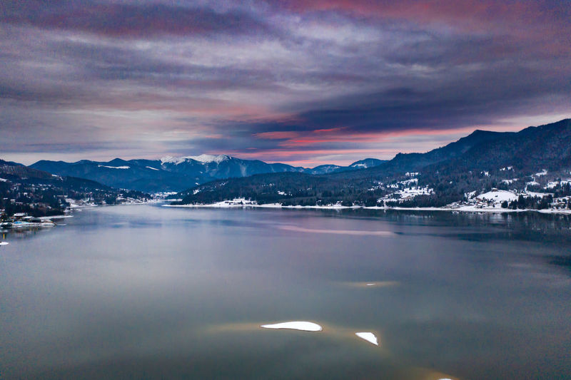 Aerial view of lake by mountains against sky during sunset