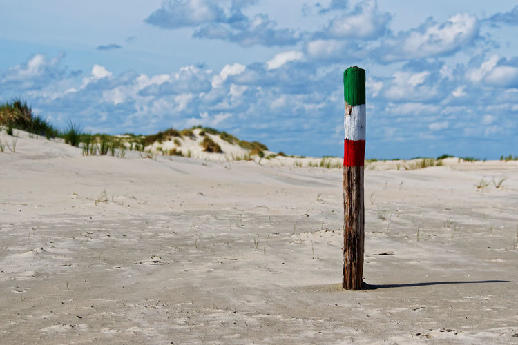 Wooden Post on the beach Land Beach No People Nature Wood - Material Focus On Foreground Outdoors Single Object Red Sand Absence Tranquil Scene Wooden Post Non-urban Scene Cloud - Sky Landscape Strand Ocean Nordsee Insel Deutschland Ostfriesland Coast Küste Coastline