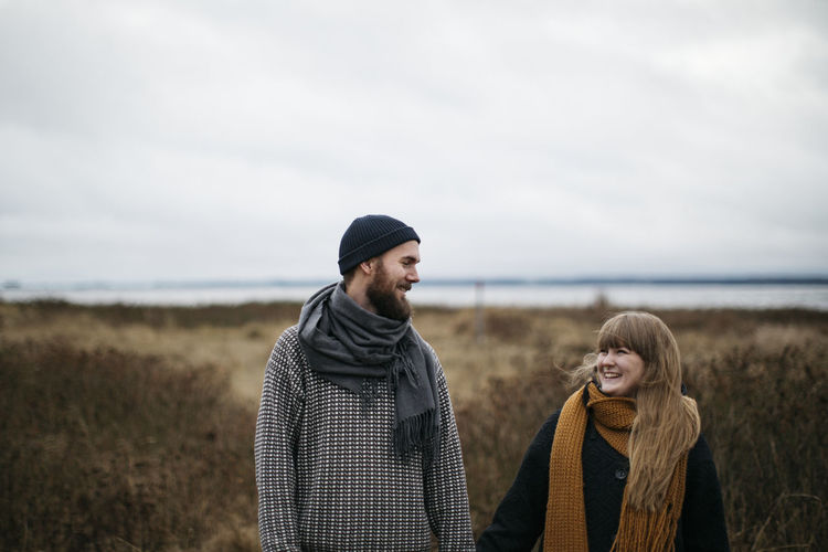 Young couple standing on land against sky