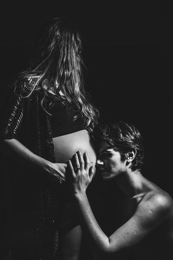 Man touching pregnant woman belly against black background
