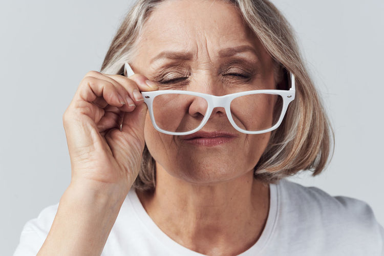 Close-up portrait of woman with eyeglasses against white background