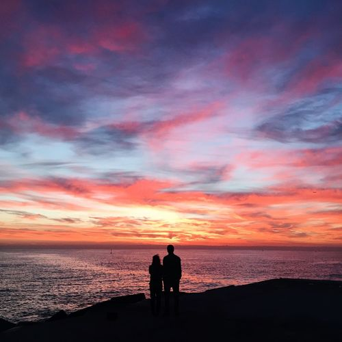 Silhouette Couple At Beach Against Orange Sky
