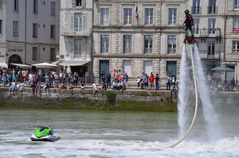Man flyboarding in sea against building in city