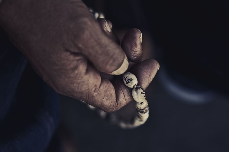 Cropped hand holding beaded bracelet