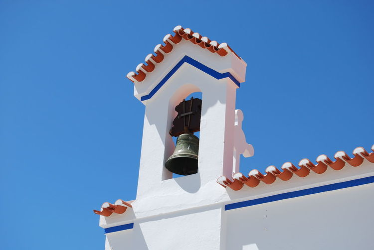 Low angle view of bell on church against clear blue sky