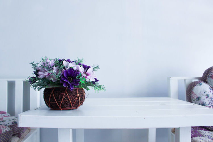 Flower pot on table against wall