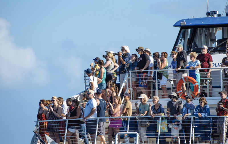 Low angle view of people standing at cruise ship against sky