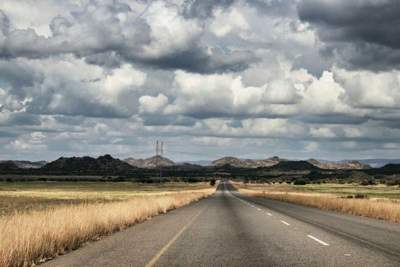 View of country road against cloudy sky