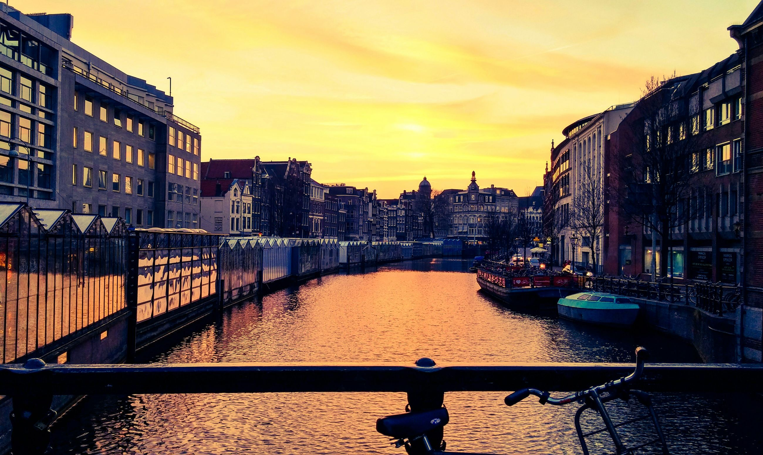 building exterior, architecture, built structure, water, sunset, city, canal, sky, railing, orange color, river, residential structure, building, transportation, bridge - man made structure, residential building, cloud - sky, outdoors, mode of transport, cityscape