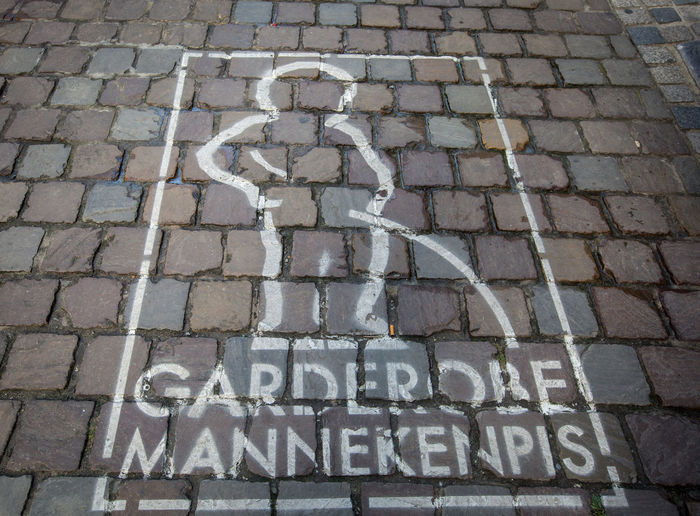 Manneken pis sign in brussels Sign Backgrounds Brick Capital Letter City Cobblestone Communication Day Footpath Full Frame High Angle View Information Mannekenpis Message No People Outdoors Pattern Paving Stone Sign Stone Street Text Western Script
