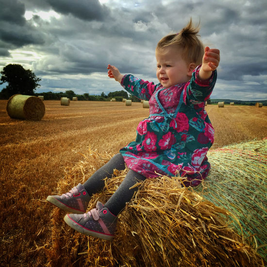 Little girl on a bale of straw in the autumn Agriculture Bale  Blond Hair Cereal Plant Childhood Cloud - Sky Day Field Full Length Girls Grass Happiness Hay Haystack Landscape Lifestyles Nature One Person Outdoors Real People Rural Scene Sky Smiling Straw Wheat