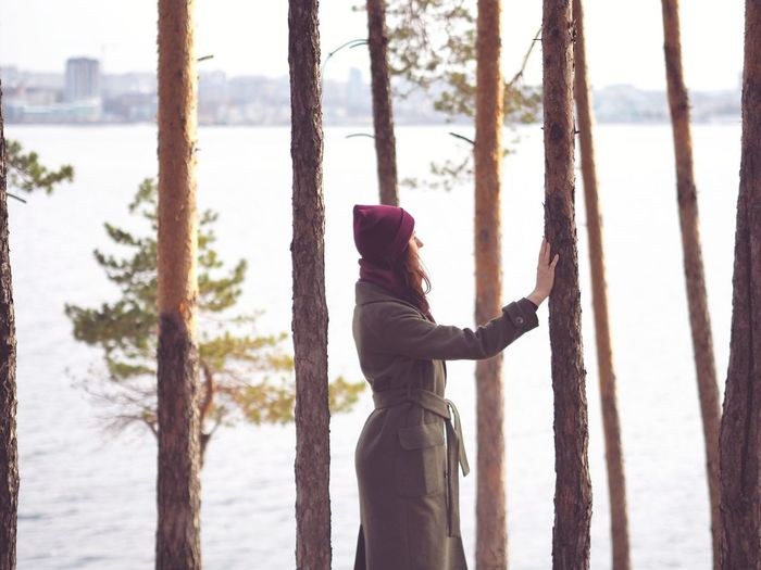 Side view of woman in warm cloth standing by trees