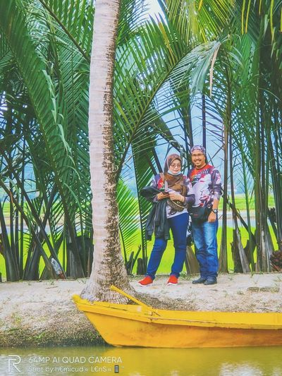 People standing by palm trees