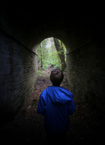 Boy in tunnel Lonely Arch Architecture Boy,  Boys Built Structure Casual Clothing Child Childhood Dark Day Males  Men One Person Outdoors Real People Rear View Solitude Solitude And Silence Standing Teenager Tunnel Waist Up