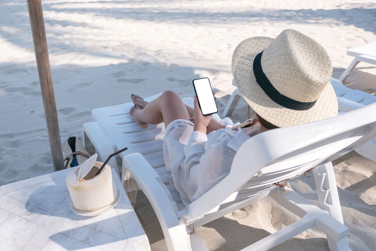 Mockup image of a woman holding white mobile phone with blank desktop screen while laying down on beach chair on the beach Smartphone Shoulder Sea Screen Sand Relax Phone People Over Online  Mockup Mock Mobile Message Look Lifestyle Laying Internet Holiday Holding Hand Girl Female Empty Down Display Device Desktop Copyspace Copy Connection Communication Chair Cellphone Cell Blank Black Beach Background