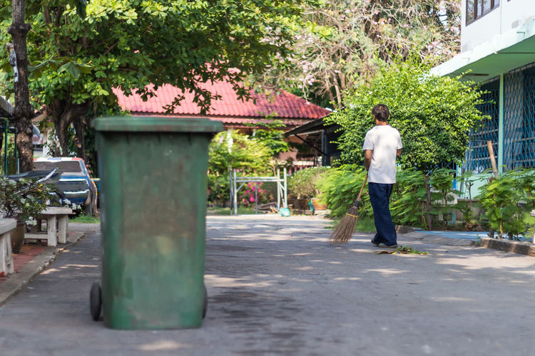 Rear view of man walking on footpath