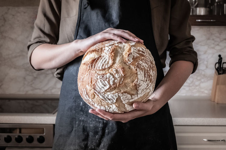 Midsection Of Baker Holding Baked Bread In Bakery