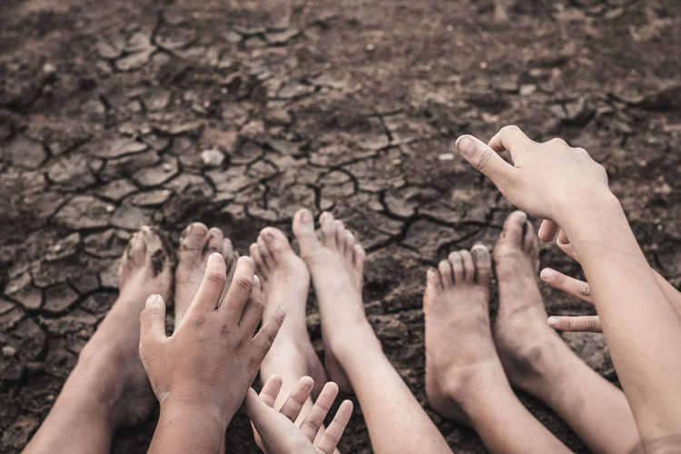 Low section of friends gesturing on drought field