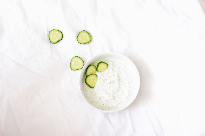 white dip in white bowl with cucumbers white background Wellness White White Background Food Cucumber Vegetable No People High Angle View Directly Above Green Color Healthy Lifestyle Studio Shot SLICE