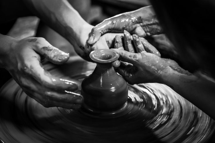 Cropped hands of people making pottery in workshop