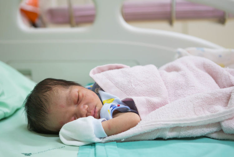 Close-Up Of Cute Newborn Sleeping On Bed At Hospital