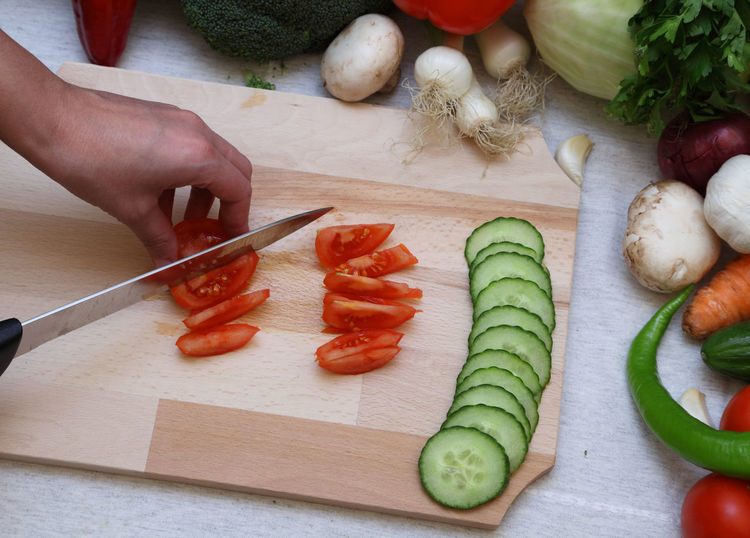 Chopping vegetables Chopping Chopping Board Cutting Cutting Board Food Food And Drink Freshness Healthy Eating High Angle View Human Hand Kitchen Knife Knife One Person Preparation  Preparing Food Raw Food Real People SLICE Table Tomato Vegetable